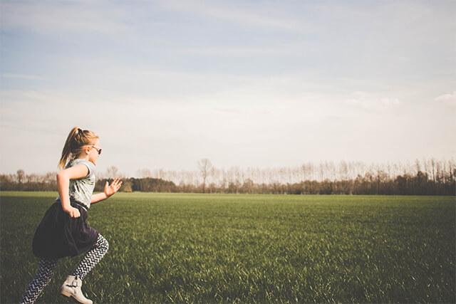芝生の上を走る女性